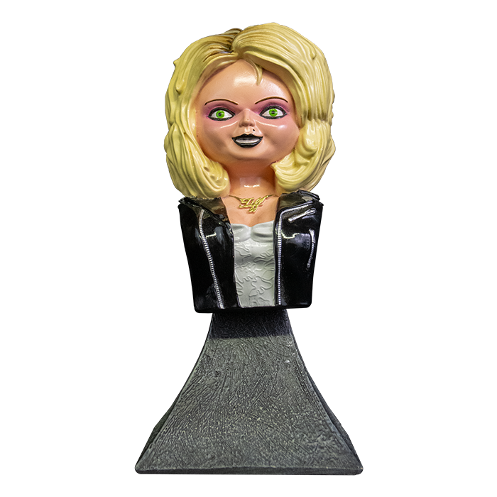 This is a Bride of Chucky Tiffany mini bust and she has blonde hair, a gold necklace, a black leather jacket with zippers, a white dress and a grey stand.