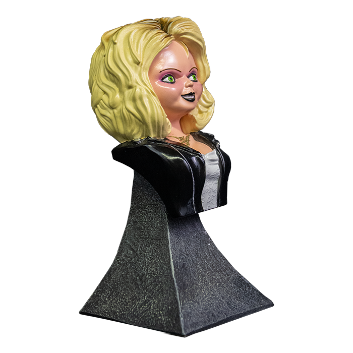 This is a Bride of Chucky Tiffany mini bust and she has blonde hair, a gold necklace, a black leather jacket with zippers, a wedding dress and a grey stand.