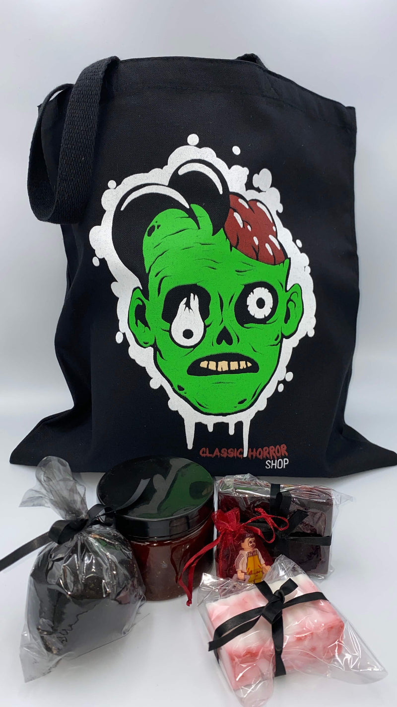 This is a bath and body set with a Classic Horror Shop zombie tote, bloody red scrub, red soap, white soap, black charcoal hemp bath bomb and a LEGO mini figure.