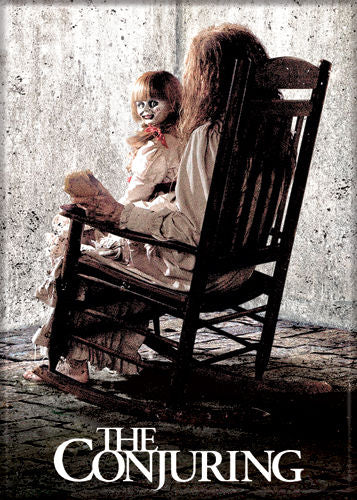 This is a Conjuring Annabelle magnet that is a creepy girl in a rocking chair with a doll wearing a white dress on her lap and with her head turned around.