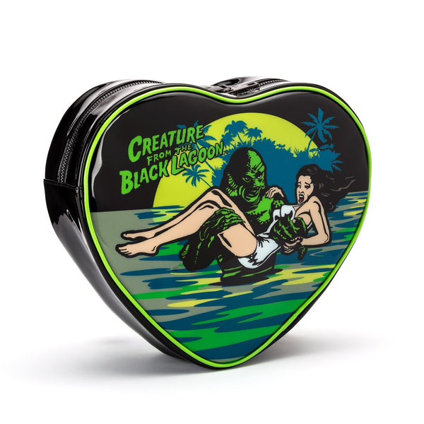 This is a Universal Monsters Creature From the Black Lagoon heart purse and backpack that is black with green piping and has a woman with dark hair and a white bathing suit being carried out of the water by a green creature.