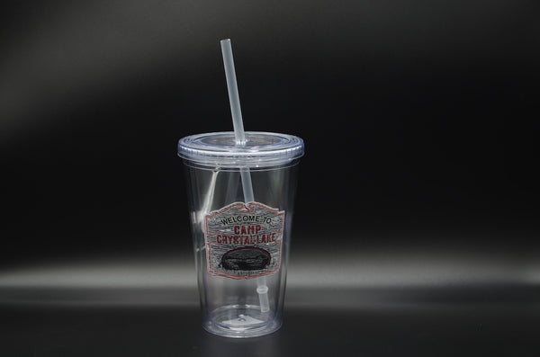 This is a Friday the 13th Camp Crystal Lake cup and straw that has a brown wooden sign with red welcome to letters.