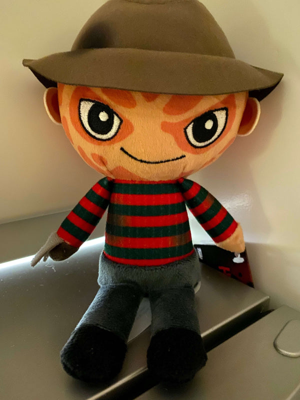 This is a Nightmare On Elm Street Freddy Krueger Funko plushie and he has a burned face and is wearing a brown hat, dirty red striped sweater, grey pants and black shoes or boots.
