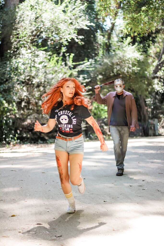 There is a camp counselor with red hair, a black camp crystal lake running team shirt and denim shorts running, while Jason Voorhees stands behind her in a hockey mask and brown shirt, while holding an axe.