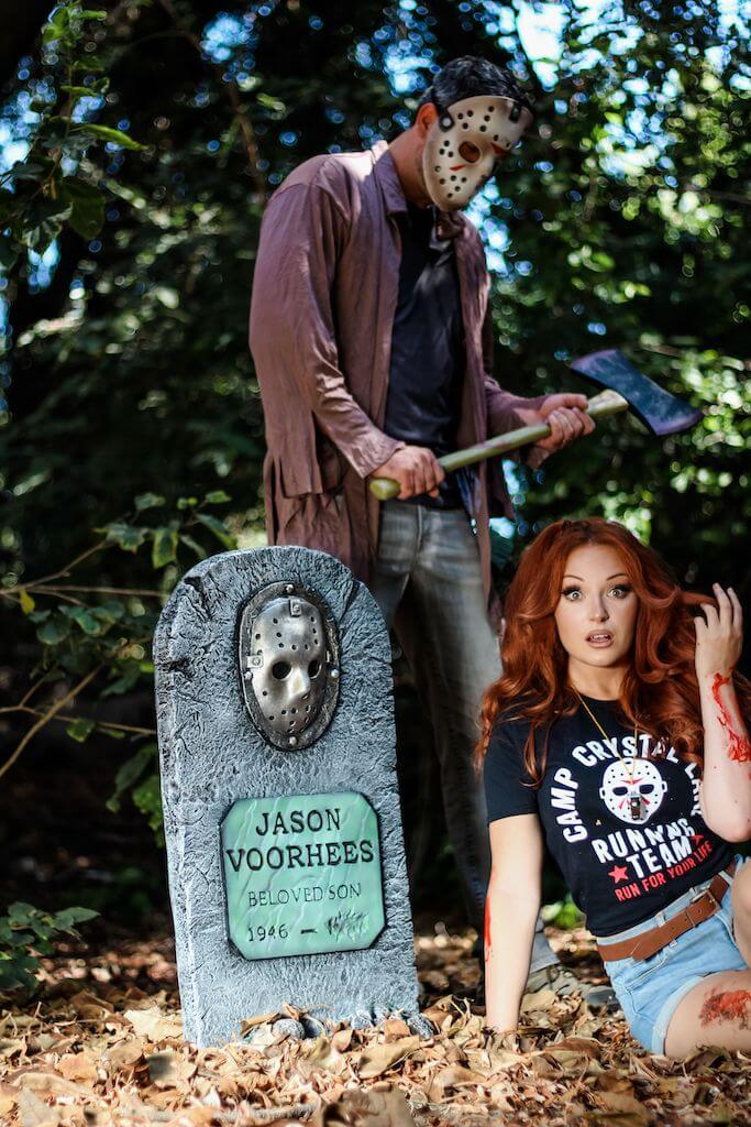 There is a girl with red hair, a black camp crystal lake running team shirt and denim shorts sitting in front of a Jason Voorhees tombstone, while he stands behind her in a hockey mask and brown shirt, while holding an axe.