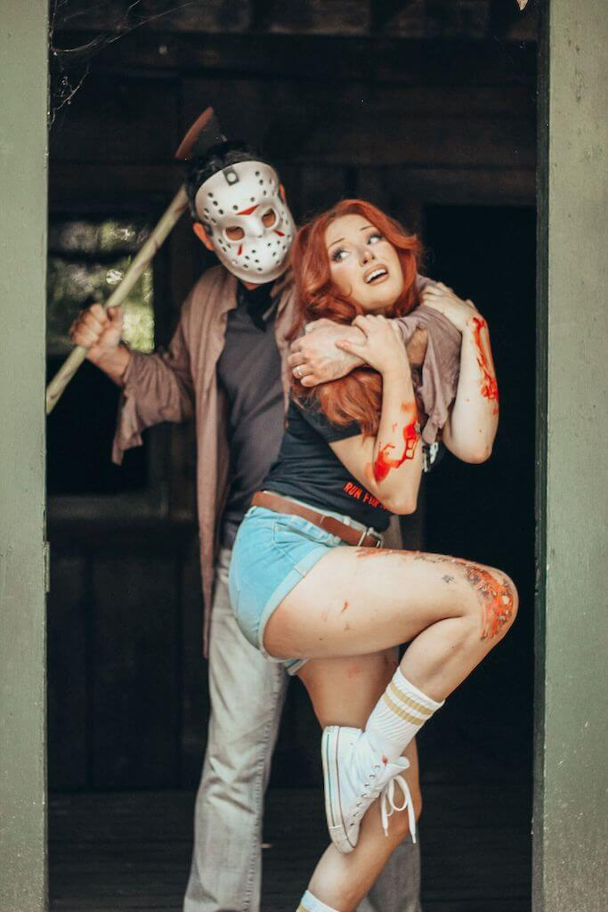 There is a camp counselor with red hair, a black camp crystal lake running team shirt and denim shorts being held, while Jason Voorhees stands behind her in a hockey mask and brown shirt, while holding an axe.
