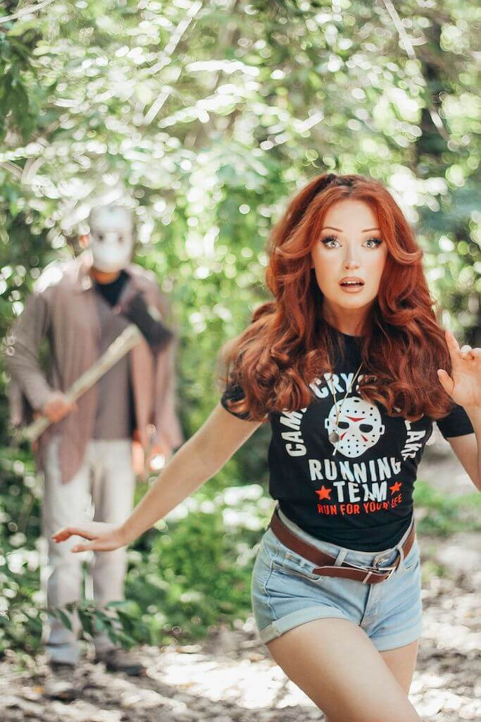 There is a girl with red hair, a black camp crystal lake running team shirt and denim shorts running, while Jason Voorhees stands behind her in a hockey mask and brown shirt, while holding an axe.