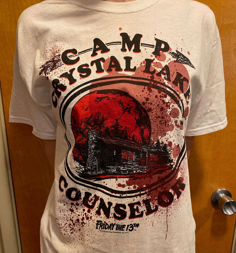 This is a Friday the 13th Camp Crystal Lake Counselor t-shirt that is white with black letters and blood and has a cabin with a red moon behind it.