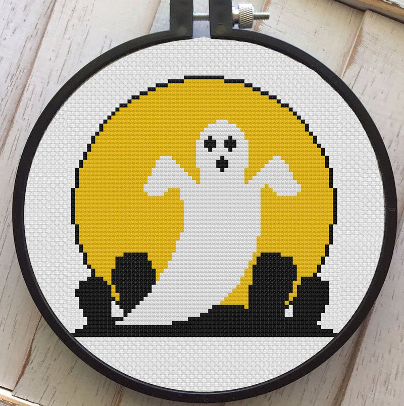 This is a DIY cross stitch kit and it has a white ghost with a yellow moon and he is in front of a cemetery.