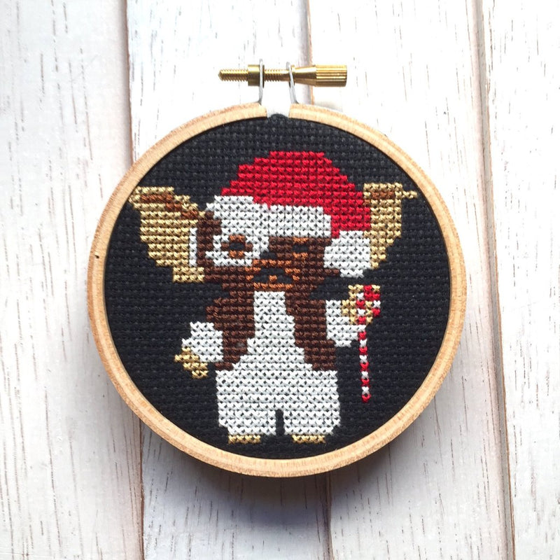 This is a Gremlins Gizmo cross stitch kit and it is black with a wooden circle hoop and he has on a red Santa hat and is holding a candy cane.