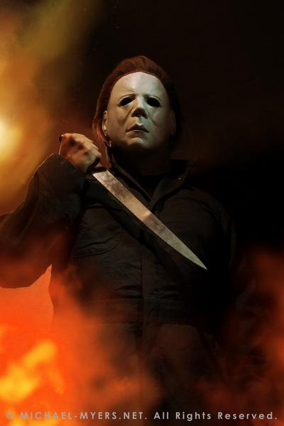 This is a Halloween II Michael Myers mask, that is a white face with brown hair and eye holes, a knife and green coveralls and fire.