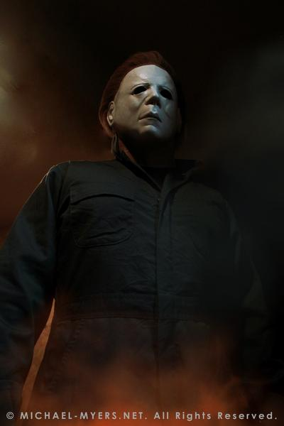 This is a Halloween II Michael Myers mask, that is a white face with brown hair and eye holes and green coveralls and fire.