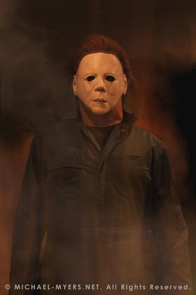 This is a Halloween II Michael Myers mask, that is a white face with brown hair and eye holes and green coveralls.