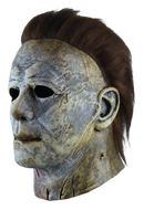 This is a weathered Michael Myers mask bloody edition from Halloween 2018 and it is a grey and brown face and ear with brown hair and black eyes.
