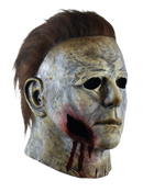 This is a weathered Michael Myers mask bloody edition from Halloween 2018 and it is a grey and brown face and ear with brown hair and black eyes and has a piece of face missing with blood coming out..