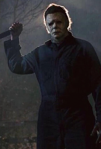 This is a Halloween 2018 Michael Myers mask that is a weathered grey face, neck and ear and has brown hair and black eyes and he is wearing grey coveralls, holding a knife and standing in front of a tree.
