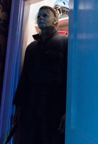 This is a Halloween 2018 Michael Myers mask that is a weathered grey face, neck and ear and has brown hair and black eyes and he is wearing grey coveralls, holding a knife and standing in a doorway.