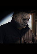 This is a Halloween 2018 Michael Myers movie still with a mask that is weathered grey face and he is wearing grey coveralls.