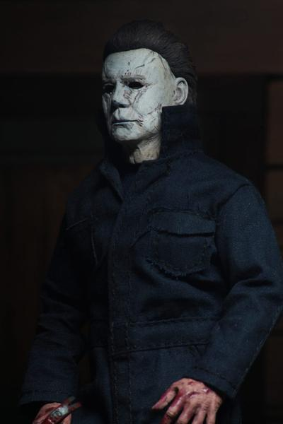 "This is a NECA 8"" clothed action figure from Halloween 2018 of Michael Myers, who is wearing a grey and weathered mask and grey coveralls."