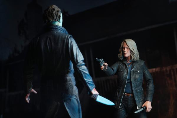 "This is a HALLOWEEN 2018 NECA 7"" Scale Action Figure Ultimate Laurie Strode and she has grey hair, glasses, a coat and a gun that she is pointing at Michael Myers, who is holding a knife and wearing coveralls."