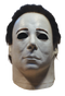 This is a Halloween 4 Return of Michael Myers mask that has a white face and neck, with dark brown hair and black eyes.