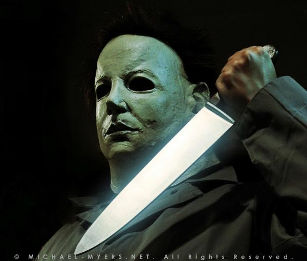 This is a Halloween 6 Curse of Michael Myers mask that is white with brown hair and black eyes and he is wearing coveralls and holding a silver knife.