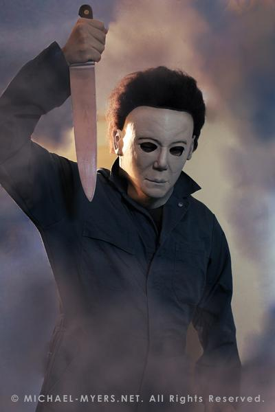 This is a Michael Myers Halloween H20 Mask that is white with brown hair and he is wearing green coveralls and holding a knife, while standing in smoke..