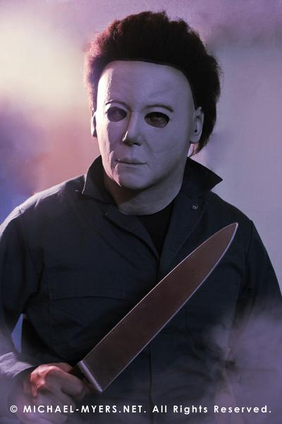 This is a Michael Myers Halloween H20 Mask that is white with brown hair and he is wearing green coveralls and holding a knife.