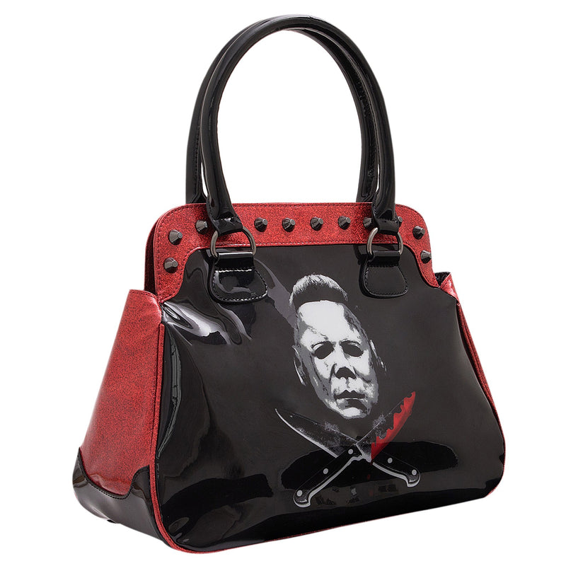 This is a Halloween Michael Myers vegan style handbag or purse that is shiny black and glitter red, with a white face and bloody crossing knives.