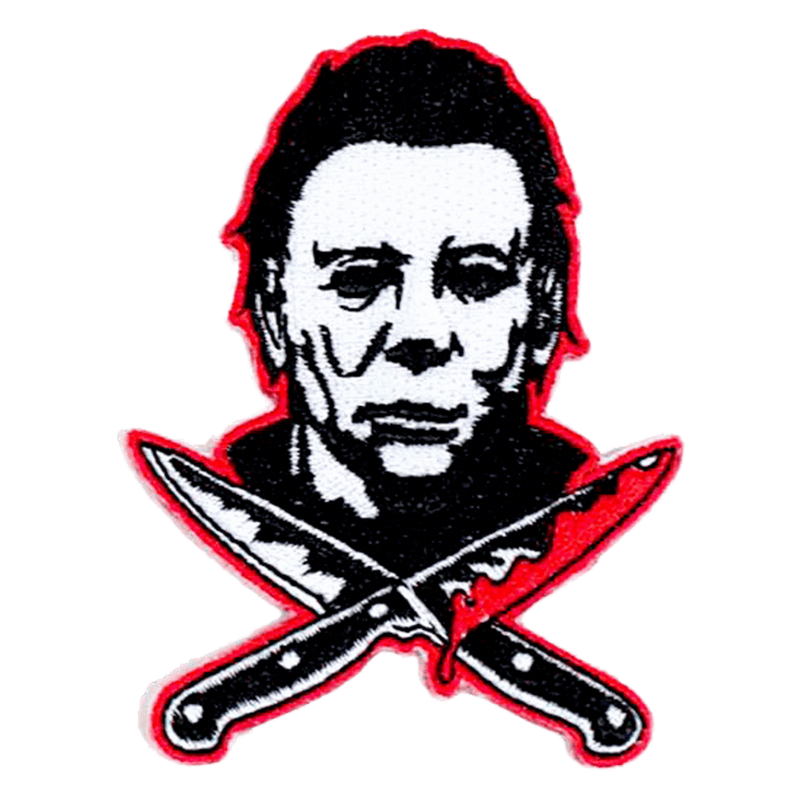 This is a Halloween Michael Myers back patch that has a white face, dark hair and two bloody knives, that are crossed.