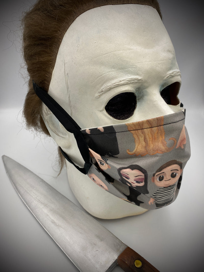 This is a grey protective face mask with black ties and has Addams Family characters Gomez, Morticia, Wednesday, Pugsley, Lurch, Uncle Fester and Cousin Itt and is on a Michael Myers mask.