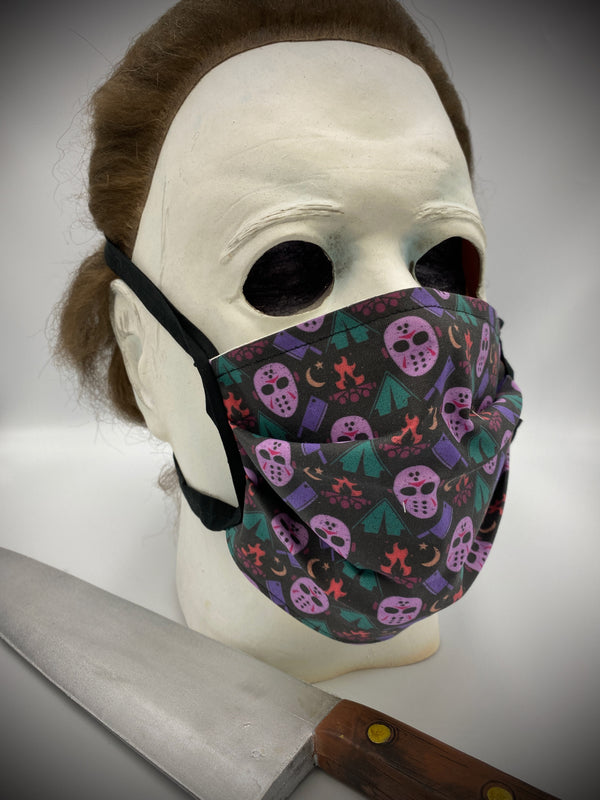 This is a black protective face mask with black ties and it is a Friday the 13th Jason Voorhees pink hockey mask and a purple butcher knife, tents and a campfire, worn by Michael Myers.