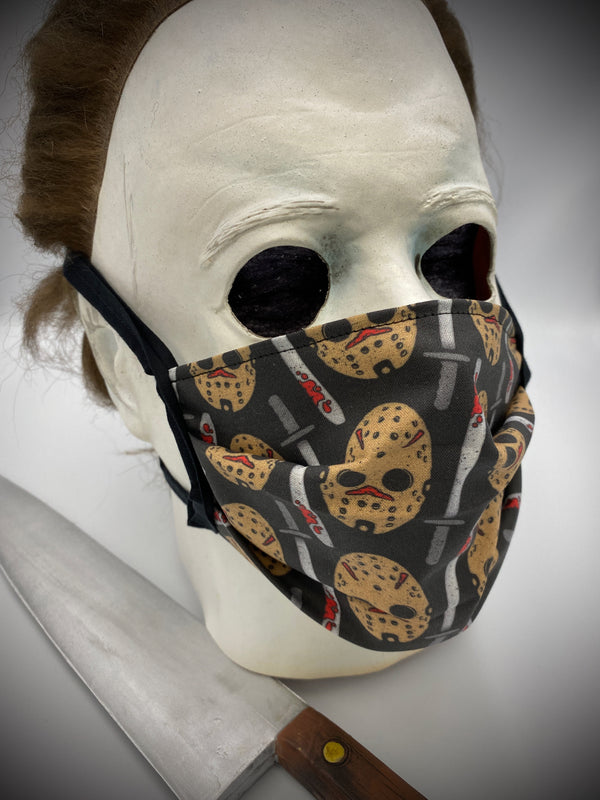 This is a black protective face mask with black ties and it is a Friday the 13th Jason Voorhees white hockey mask and a machete with blood on it, worn by Michael Myers.