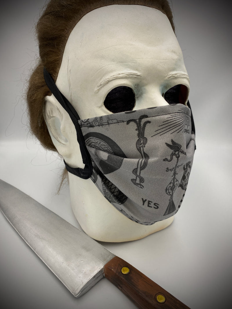 This is a black protective face mask with black ties and it has a ouija board, skeleton, octopus, skulls and bottles, worn by Michael Myers.