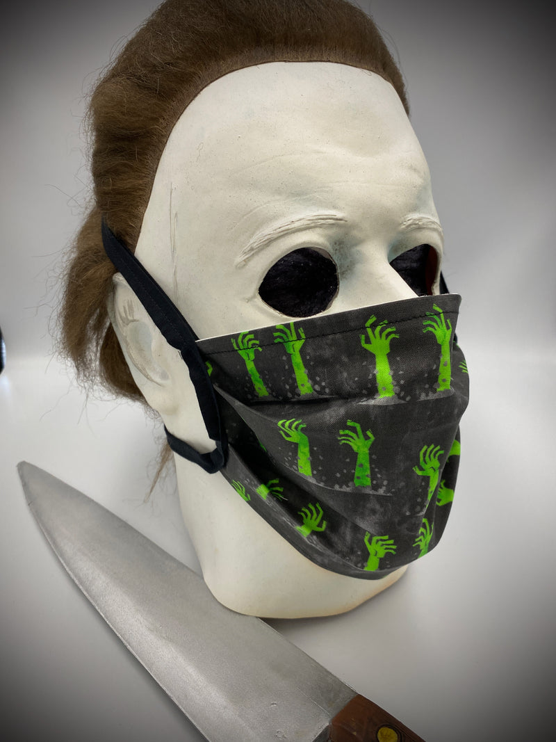 This is a black protective face mask with black ties and it has green zombie arms and hands coming out of the dirt, worn by Michael Myers.