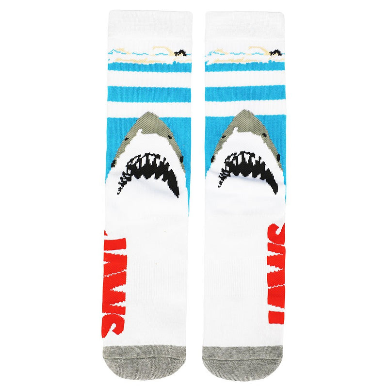 This is a pair of Jaws crew socks and there is a girl swimming in the blue water and a shark with pointy teeth below her.