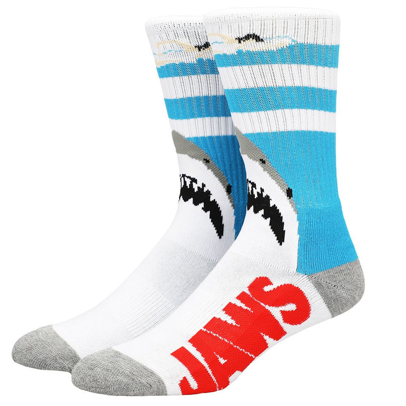 This is a pair of Jaws crew socks and there is a girl swimming in the water and a shark below her.