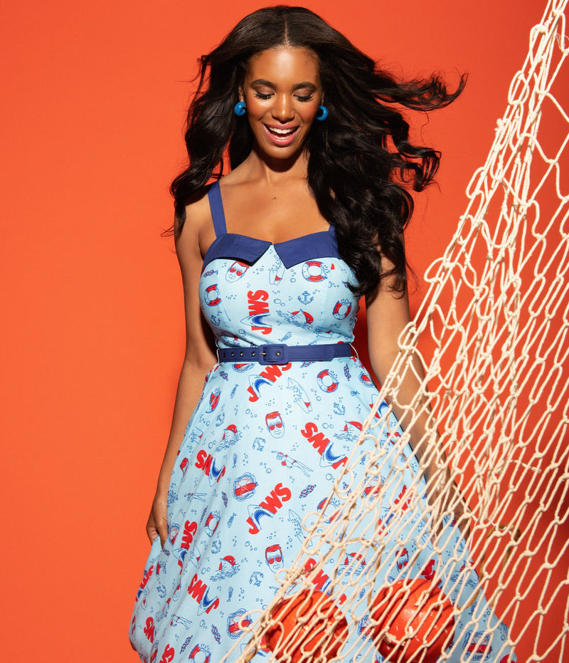 This is a Unique Vintage Jaws dress and the model has dark hair and the dress is blue with red text and sharks on it, Chief Brody and anchors and she has a net on her with an orange background.