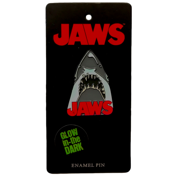 This is a Jaws enamel pin and he is grey with sharp teeth and the logo is in red font.