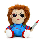 This is a Child's Play Chucky Kidrobot HugMe vibrating plush and he has a striped shirt, red shoes, orange hair and is holding a bloody silver knife with a black handle.