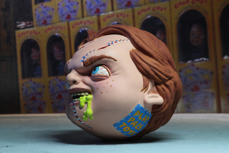 Chucky has red hair, scars on his face, his head is a 4 inch ball and he has green stuff coming out of his foam head.
