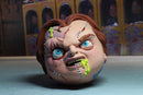 Chucky has red hair, scars on his face, his head is a Madball and he has green stuff coming out of his foam head.