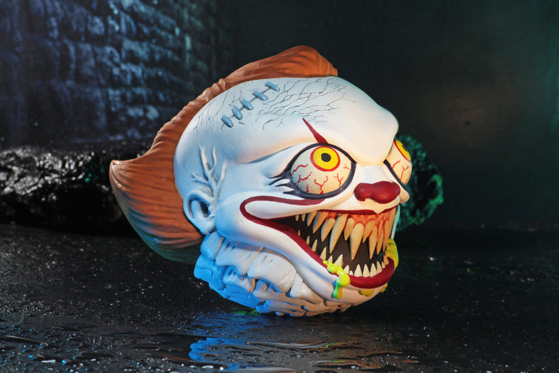 Pennywise the clown from the It movie has green goo coming out of his mouth, that is showing his fang teeth, below his orange hair..