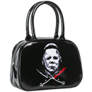 This is a Halloween Michael Myers bowler style handbag or purse that is shiny black, with a white face and bloody crossing knives.