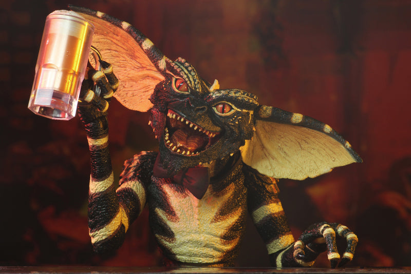 This is a NECA Gremlins flasher ultimate action figure and he is holding a draft beer in a clear mug.