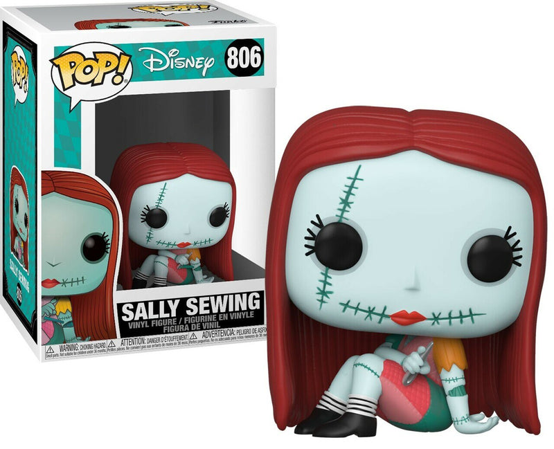 This is a Nightmare Before Christmas Sally Funko Pop and she is blue, sitting with a colored stitched dress on and holding a silver sewing needle.