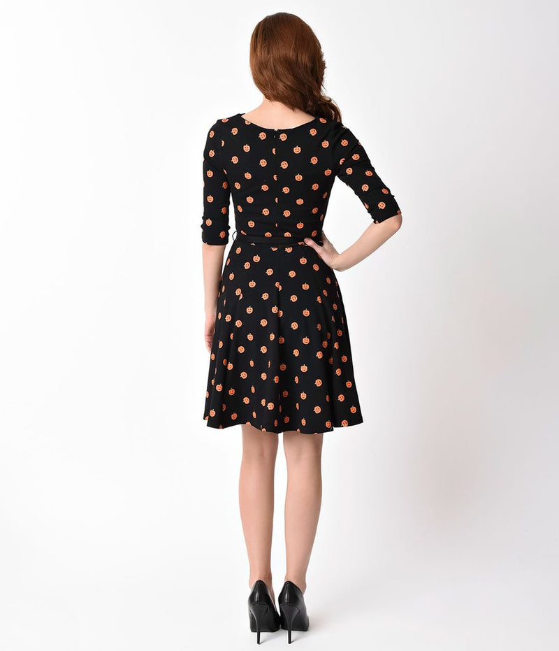 This is a black pinup flare dress with orange pumpkins, belt and 3/4 sleeves and the model is wearing black shoes and has brown hair to the side.
