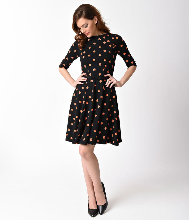 This is a black pinup flare dress with orange pumpkins, belt and 3/4 sleeves and the model is wearing black shoes and has brown hair.