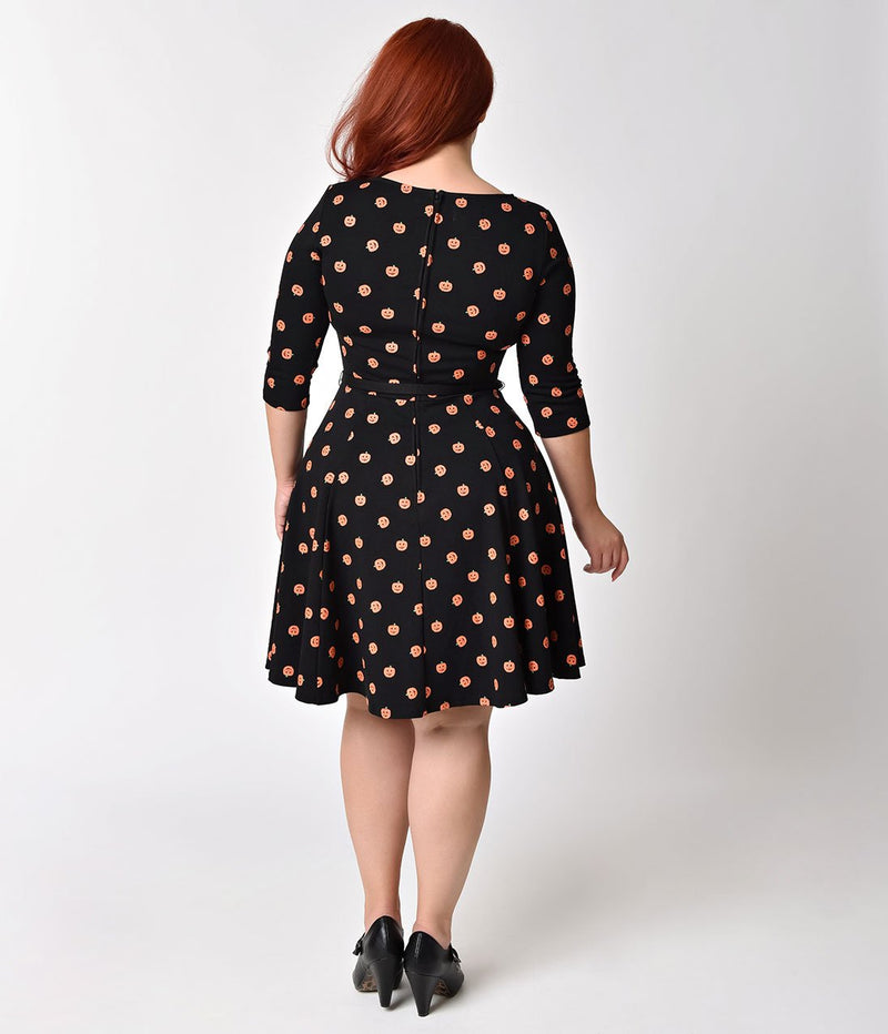 This is a black pinup flare dress with orange pumpkins and 3/4 sleeves, belt and the plus model is wearing black shoes.