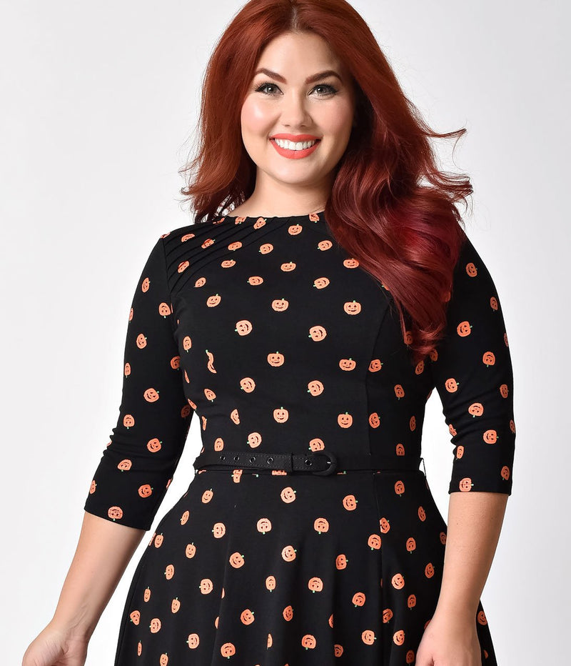 This is a black pinup flare dress with orange pumpkins and 3/4 sleeves, belt and the plus model is smiling and has red hair.